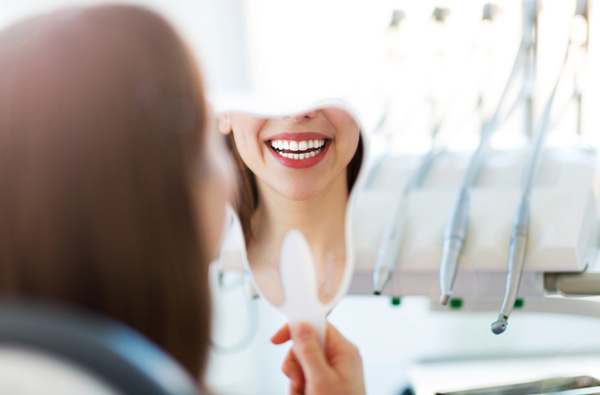 Woman looking at her smile in a mirror after receiving restorative dentistry from Lanier Valley Dentistry